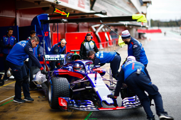 Circuit de Catalunya, Barcelona, Spain. Wednesday 28 February 2018. Brendon Hartley, Toro Rosso STR13 Honda, is wheeled back into his pit garage by mechanics. World Copyright: Andy Hone/LAT Images ref: Digital Image _ONY9858