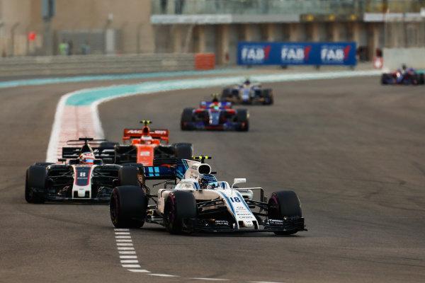 Yas Marina Circuit, Abu Dhabi, United Arab Emirates. Sunday 26 November 2017. Lance Stroll, Williams FW40 Mercedes, leads Romain Grosjean, Haas VF-17, and Stoffel Vandoorne, McLaren MCL32 Honda. World Copyright: Sam Bloxham/LAT Images  ref: Digital Image _W6I4308