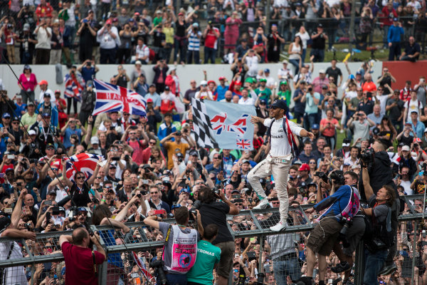 Silverstone, Northamptonshire, UK Sunday 10 July 2016. Lewis Hamilton, Mercedes AMG, 1st Position, celebrates victory at his home race with the fans. World Copyright: Ferraro/LAT Photographic ref: Digital Image _FER9049