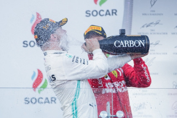 Valtteri Bottas, Mercedes AMG F1, 1st position, sprays the victory Champagne into his face and Sebastian Vettel, Ferrari, 3rd position, joins in