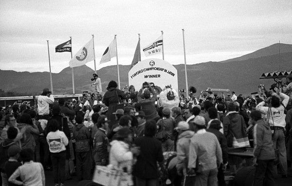 James Hunt (GBR) McLaren, celebrates winning the 1976 F1 World Championship on the podium as Mario Andretti (USA) Lotus, enjoys his race victory. Japanese Grand Prix, Rd16, Fuji, Japan, 24 October 1976.