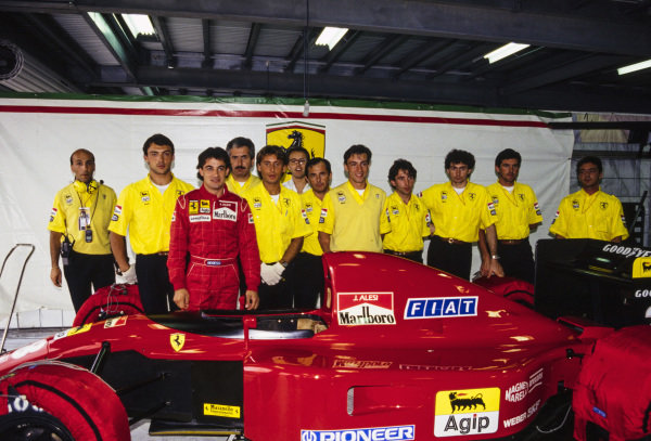 Jean Alesi with his Ferrari 643 and the team in the garage.