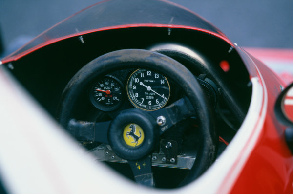 Ferrari 312T cockpit, showing steering wheel, rev counter, temperature gauge and front roll bar.