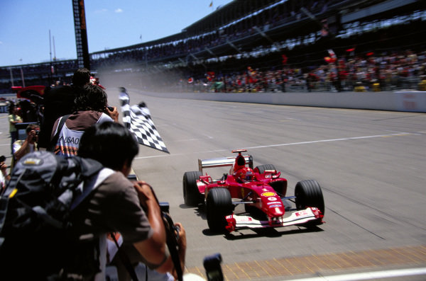Michael Schumacher, Ferrari F2004 takes the chequered flag for victory.
