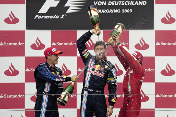 Mark Webber celebrates victory on the podium with teammate Sebastian Vettel, 2nd position, and Felipe Mass, 3rd position.