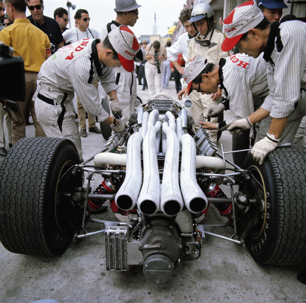 Richie Ginther waits beside his Honda RA273 as mechanics work on the engine.