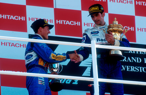 1994 British Grand Prix.Silverstone, England.8-10 July 1994.Damon Hill (Williams Renault) 1st position is congratulated by Michael Schumacher (Benetton Ford) 2nd position, but later disqualified for overtaking on the parade lap.Ref-94 GB 15.World Copyright - LAT Photographic