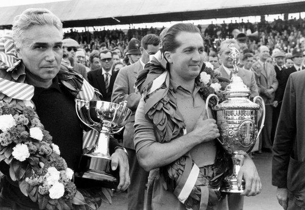 1952 British Grand Prix. Silverstone, Great Britain. 19 July 1952. Left-to-right: Piero Taruffi (Ferrari 500), 2nd position and Alberto Ascari (Ferrari 500), 1st position, on the podium. Portrait. World Copyright: LAT Photographic Ref: 19752D/38A