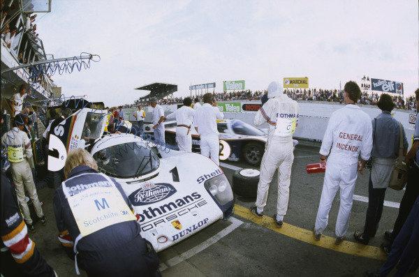 Le Mans, France. 15th - 16th June 1985.Jacky Ickx/Jochen Mass (Porsche 962C), 10th position, pit stop and driver change as team mate Derek Bell/Hans-Joachim Stuck (Porsche 962C), 3rd position, drive past, action. World Copyright: LAT Photographic.Ref: 85LM07.