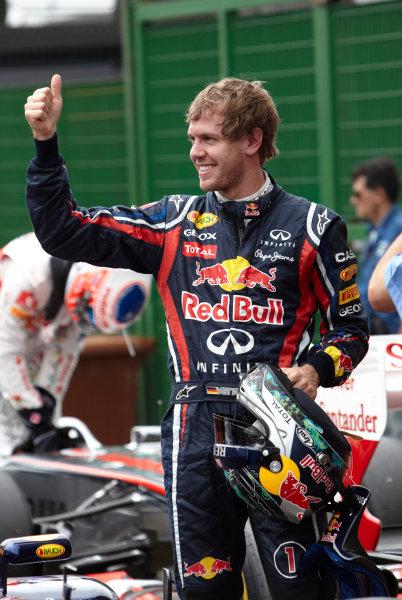 Interlagos, Sao Paulo, Brazil. 26th November 2011. Sebastian Vettel, Red Bull Racing RB7 Renault, celebrates pole in Parc Ferme. Portrait. Helmets.  World Copyright: Steve Etherington/LAT Photographic ref: Digital Image SNE27486