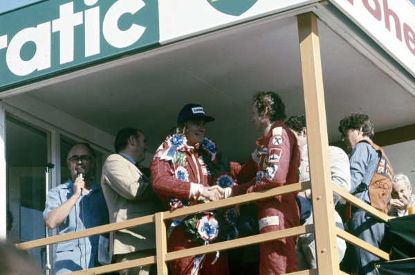 James Hunt celebrates victory on the podium Niki Lauda, 2nd position. Hunt would later be disqualified from the results, promoting Lauda to the victor.