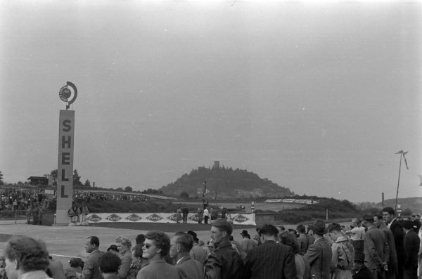 Fans watch the race as Kenneth McAlpine, Connaught A Francis, heads around in the shadow of Nurburg castle.