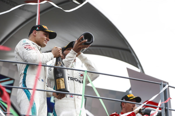 Valtteri Bottas, Mercedes AMG F1, 3rd position, and Lewis Hamilton, Mercedes AMG F1, 1st position, celebrate with Champagne on the podium.