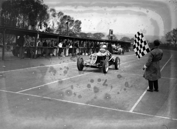 Whitney Straight, Maserati, crosses the line and takes the chequered flag.