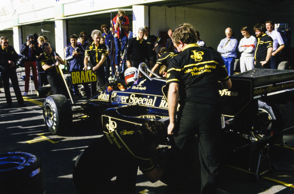 Elio de Angelis, Lotus 95T Renault, is worked on in the pits. Designer Gerard Ducarouge, mechanic Bob Dance, team manager Peter Warr and Nigel Mansell look on.