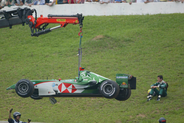 2004 Brazilian Grand Prix-Sunday Race,Sao Paulo, Brazil. 24th October 2004.Mark Webber's Jaguar R5 is removed by a crane as the Australian sits and watches the race.World Copyright LAT Photographic/Martyn Elford.Digital Image only (a high res version is available on request).