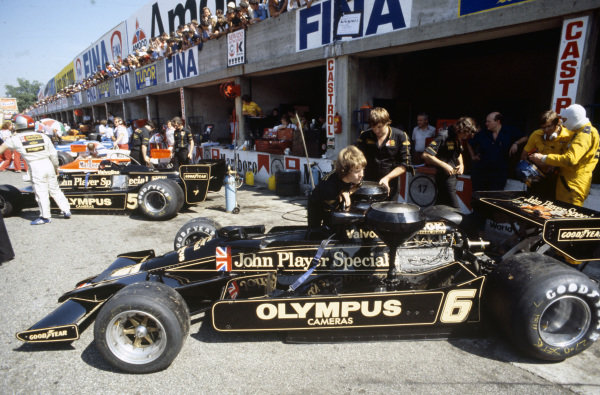 Mechanics refuel Ronnie Peterson's Lotus 78 Ford as he prepares to get into the car. Mario Andretti stands beside his car in the background.