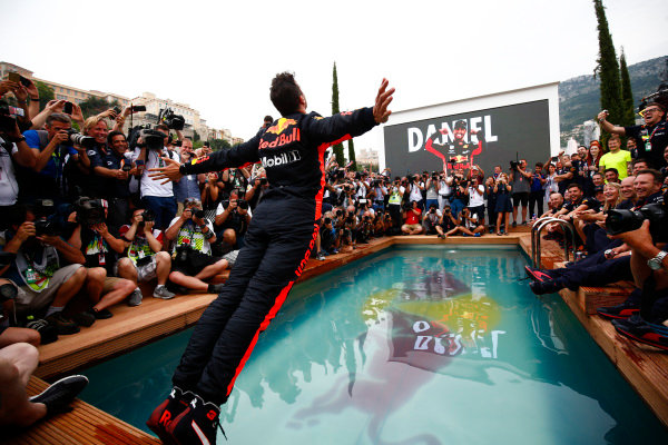 Daniel Ricciardo, Red Bull Racing, dives into the swimming pool on the Red Bull Energy Station, surrounded by a crowd of photographers and onlookers.