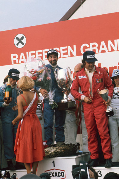 Osterreichring, Zeltweg, Austria. 13th - 15th August 1976.  John Watson (Penske PC4-Ford), 1st position celebrates taking his maiden Grand Prix win and Penske's only victory with Jacques Laffite (Ligier JS5-Matra), 2nd position and Gunnar Nilsson (Lotus 77-Ford), 3rd position on the podium, portrait. World Copyright: LAT Photographic  Ref: 76 AUT 11.