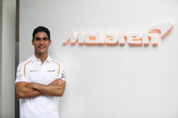 Sergio Sette Camara, McLaren test and development driver, poses next to a McLaren sign.
