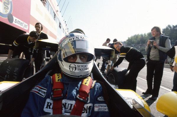 Derek Warwick, Renault RE50, sits in his cockpit with the visor raised, as mechanics lift the rear bodywork.