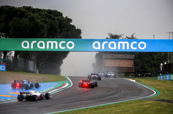 Fernando Alonso, Alpine A521, leads Sebastian Vettel, Aston Martin AMR21, Nicholas Latifi, Williams FW43B, and Nikita Mazepin, Haas VF-21