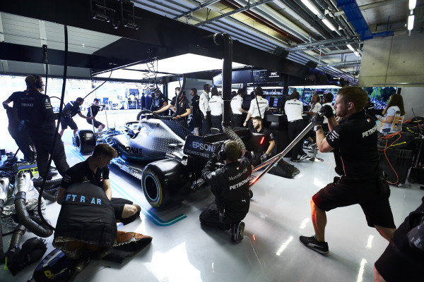 Mechanics make final preparations to the car of Valtteri Bottas, Mercedes AMG W10, in the garage