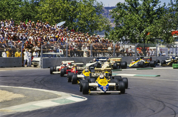 Nigel Mansell, Williams FW10 Honda, leads Ayrton Senna, Lotus 97T Renault, Keke Rosberg, Williams FW10 Honda, and Michele Alboreto, Ferrari 156/85, at the start.