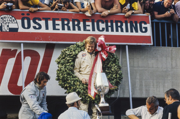 Ronnie Peterson celebrates victory on the podium with Jackie Stewart, 2nd position.