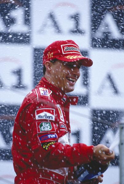 1999 Austrian Grand Prix.A1 Ring, Zeltweg, Austria.23-25 July 1999.Eddie Irvine (Ferrari) celebrates his 1st position on the podium.Ref-99 AUT 01.World Copyright - LAT Photographic