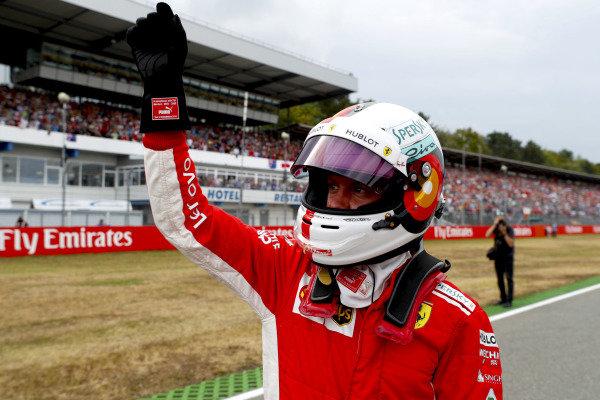 Sebastian Vettel, Ferrari, waves to fans after taking pole position.