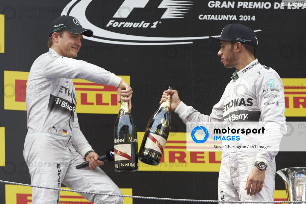 Circuit de Catalunya, Barcelona, Spain. Sunday 11 May 2014. Nico Rosberg, Mercedes AMG, 2nd Position, and Lewis Hamilton, Mercedes AMG, 1st Position, clink their Champagne bottles in celebration. World Copyright: Steve EtheringtonLAT Photographic. ref: Digital Image SNE15503 copy