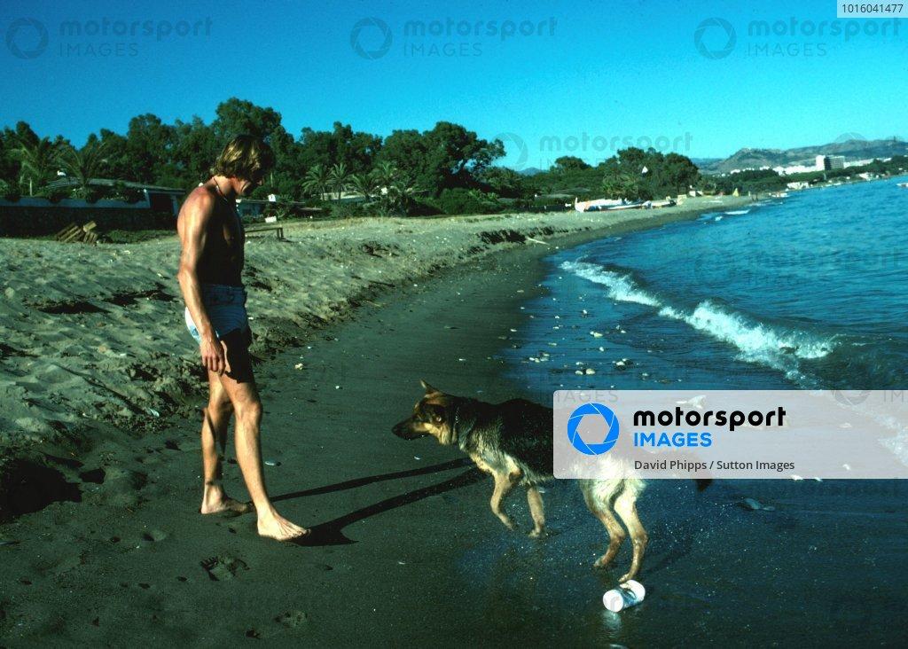 James Hunt(GBR) 1977 with dog Oscar on beach near his home in Marbella