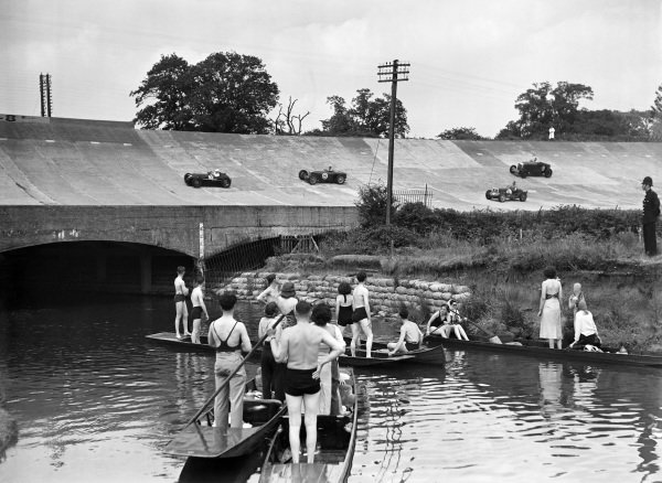 Boaters on the River Wey spectate as cars pass on the banking above them.