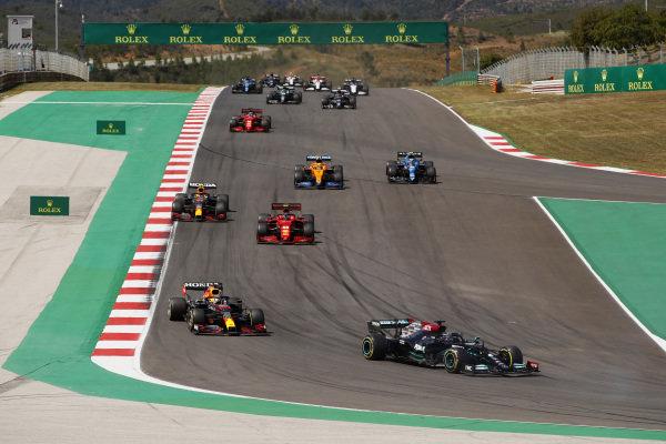 Sir Lewis Hamilton, Mercedes W12, leads Max Verstappen, Red Bull Racing RB16B, Charles Leclerc, Ferrari SF21, Sergio Perez, Red Bull Racing RB16B, Lando Norris, McLaren MCL35M, Esteban Ocon, Alpine A521, and the remainder of the field