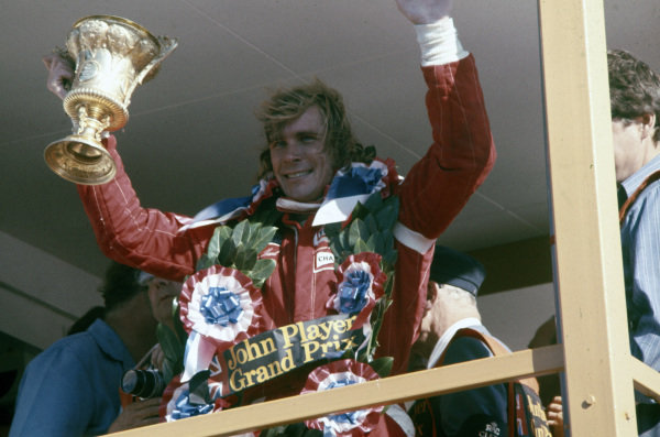 James Hunt celebrates victory on the podium. He would late be disqualified from the results.