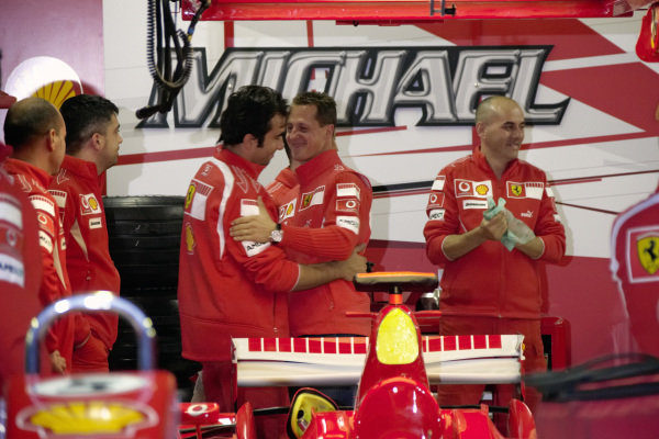 Michael Schumacher receiving well wishes from his mechanics at his last race weekend.
