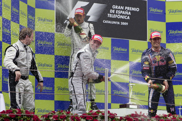 Winner Jenson Button, teammate Rubens Barrichello, 2nd position, and Mark Webber, 3rd position, celebrate on the podium.