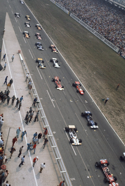 Start action. The lead two rows have already departed, leaving Chris Amon, March 701 Ford, retired to head Henri Pescarolo, Matra MS120, 6th, Pedro Rodriguez, BRM P153, retired, Jackie Stewart, March 701 Ford, retired, Mario Andretti, March 701 Ford, retired, John Miles, Lotus 72C Ford, retired and the rest of the pack.
