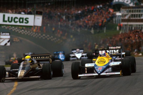 First time race winner Nigel Mansell (GBR) Williams FW10 (right) challenges pole sitter and third place finisher Ayrton Senna (BRA) Lotus 97T into Paddock Hill Bend. European Grand Prix, Rd14, Brands Hatch, England, 6 October 1985.