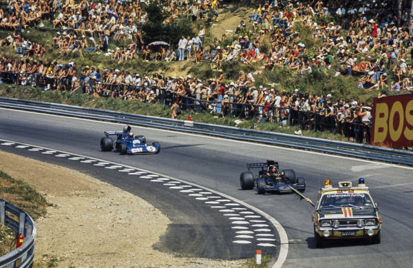 A pace car leads Emerson Fittipaldi, Lotus 72E Ford and Jackie Stewart, Tyrrell 006 Ford around the track, waving a green flag.