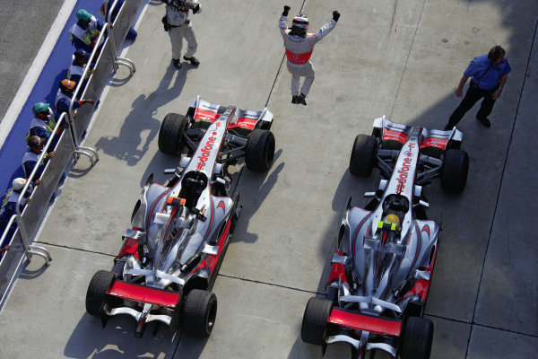 Fernando Alonso leaps in celebration at his victory in parc fermé as teammate Lewis Hamilton still sits in his McLaren MP4-22 Mercedes.