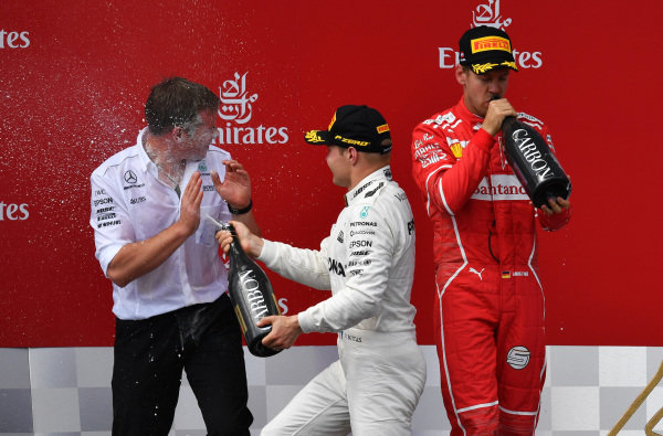 Valtteri Bottas (FIN) Mercedes AMG F1 and Sebastian Vettel (GER) Ferrari celebrate on the podium with the champagne at Formula One World Championship, Rd9, Austrian Grand Prix, Race, Spielberg, Austria, Sunday 9 July 2017.