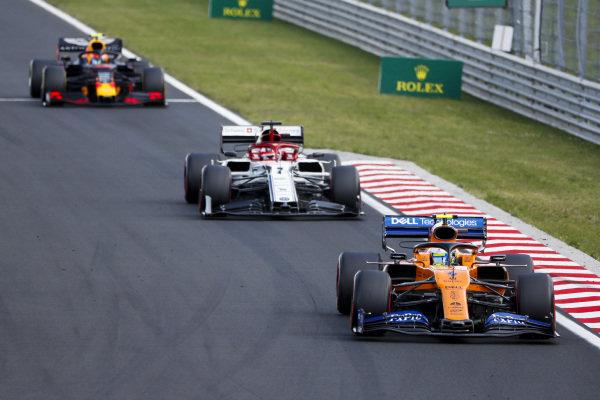 Lando Norris, McLaren MCL34, leads Kimi Raikkonen, Alfa Romeo Racing C38, and Pierre Gasly, Red Bull Racing RB15