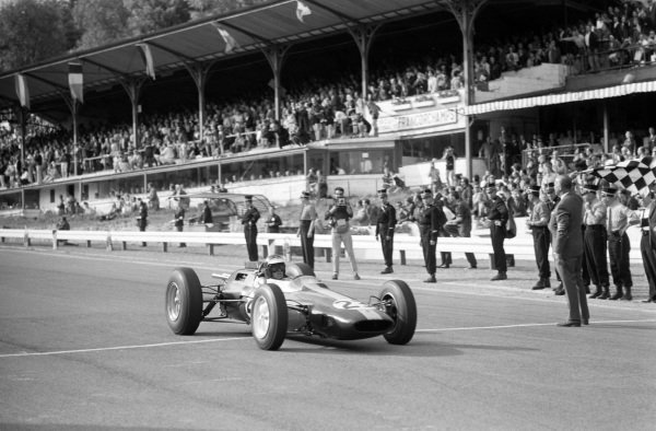 Jim Clark, Lotus 25 Climax, takes the chequered flag for victory.