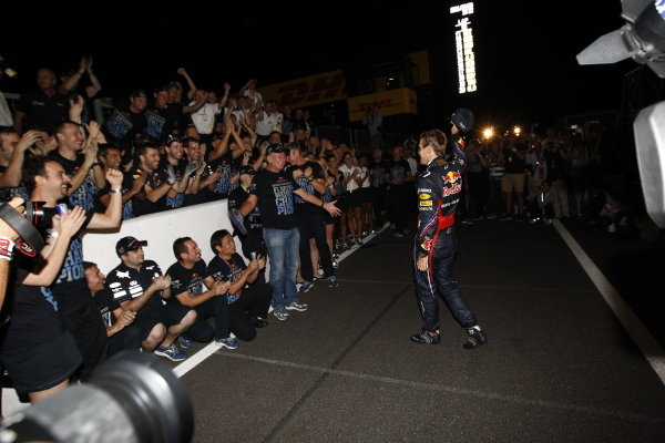 Sebastian Vettel is greeted by the Red Bull team to celebrate securing the drivers' world championship.