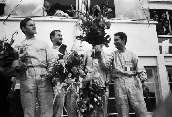 Nino Vaccarella and Jean Guichet celebrate with second-placed Jo Bonnier and Graham Hill on the podium.