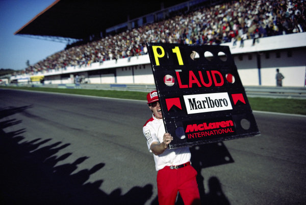 A McLaren mechanics celebrates with a pitboard as Niki Lauda becomes World Champion.