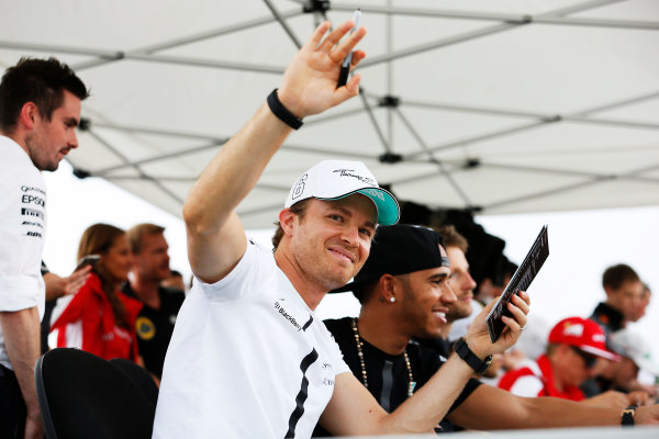 Hungaroring, Budapest, Hungary. Thursday 23 July 2015. Nico Rosberg, Mercedes AMG, and Lewis Hamilton, Mercedes AMG, sign autographs for fans. World Copyright: Charles Coates/LAT Photographic ref: Digital Image _J5R0529