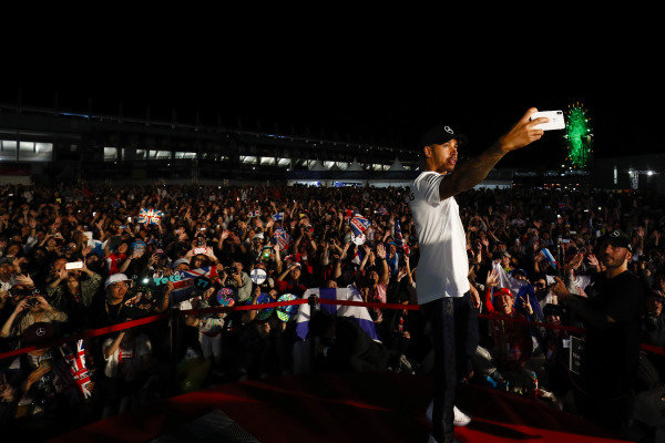Lewis Hamilton, Mercedes AMG F1, takes a photo with the crowd from the stage